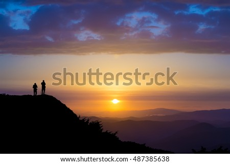 Silhouettes of two people standing on a rock and looking toward the sun. Dramatic clouds over them. Sunset in the mountains. Purple light. Summer in the Ukrainian Carpathians