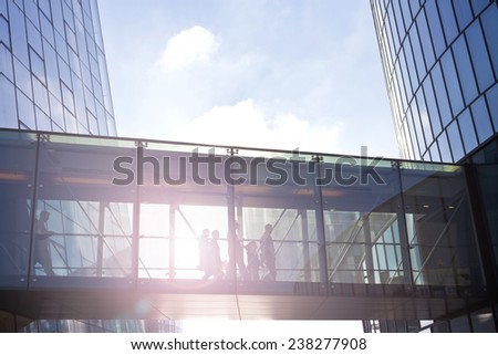 Silhouettes of unrecognizable business people using a transition between two contemporary office buildings. - stock photo