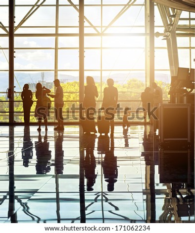 Silhouettes of unrecognizable traveling people at the airport in front of huge window with nature landscape in the background - stock photo