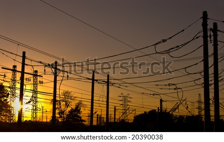 silhouettes of wires and pillars on sunset