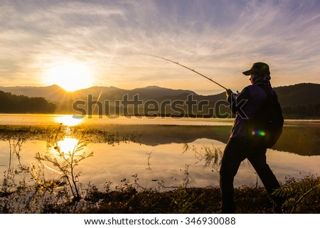 Silhouettes of young Asia man fishing on the lake with fair sun light early in the morning at sunrise time - stock photo