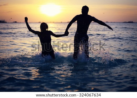 Silhouettes of young couple jumping in sea on sunset