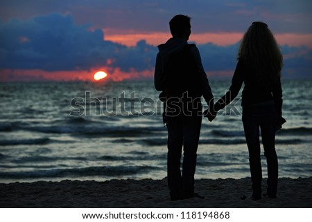 Silhouettes of young family romantic couple at sunset beach - stock photo