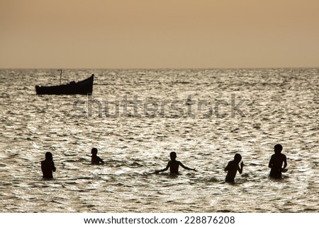 Silhouettes of young group of people having fun in ocean at sunset in Morocco with a small boat in the background. - stock photo