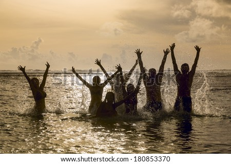 Silhouettes of young group of people jumping in ocean at sunset. - stock photo