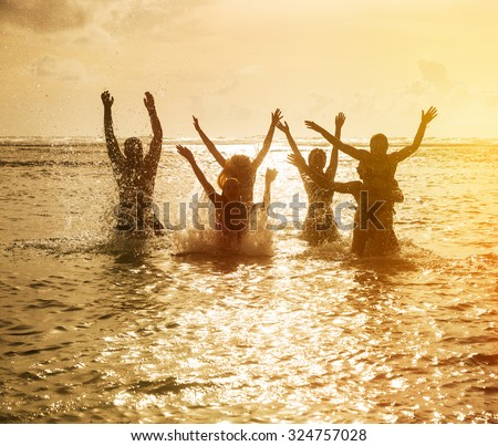 Silhouettes of young group of people jumping in ocean at sunset