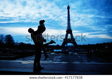 Silhouettes of young romantic couple near the Eiffel tower in Paris, France - stock photo