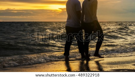 silhouettes on beach at sunset