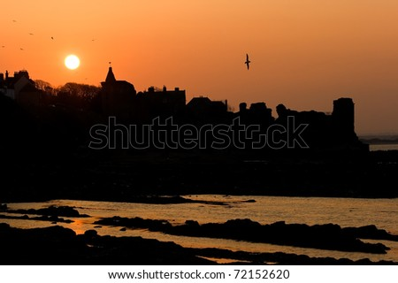 Silhouettes over the castle in St Andrews at sunset. - stock photo