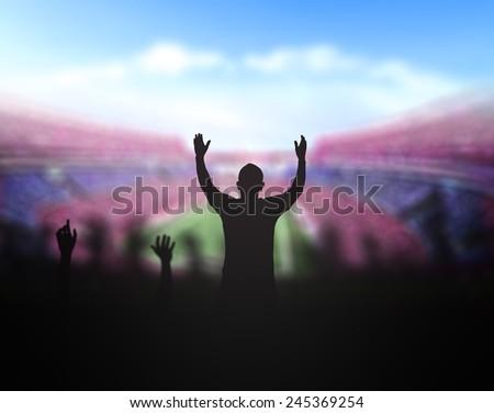 Silhouettes people raising hands over stadium. - stock photo