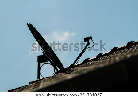 Silhouettes Satellite dish and TV antennas on the house roof