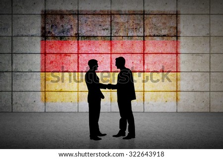 Silhouettes shaking hands against germany flag in grunge effect