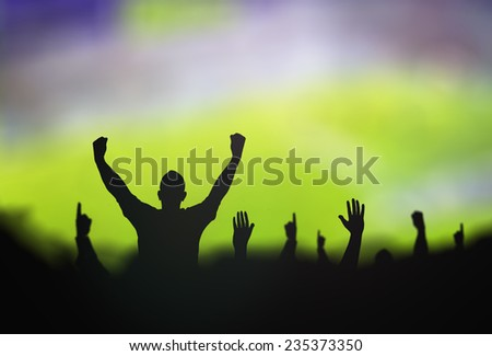 Silhouettes soccer fans club raising hands over stadium. - stock photo