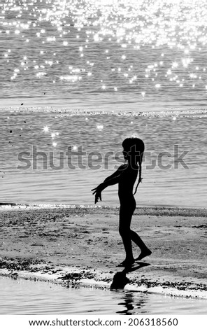Silhouetto of a little girl in counter light on a river bank, monochrome - stock photo