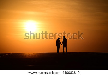 silhoutte of a couple walking and enjoying the evening sunset with yellow orange sun and bright yellow sky in the background.