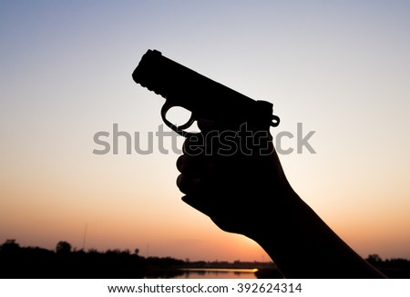 Silhoutte of a man with a handgun at sunset - stock photo