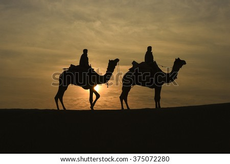 Silhoutte of Camel Trader in the Thar Desert during sunrise. Thar Desert located at Jaisalmer, Rajastan, India.