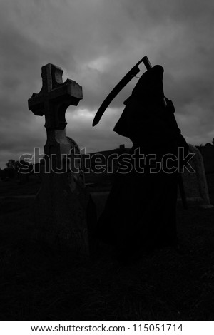 Silhoutte of the grim reaper in a graveyard - stock photo