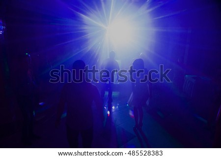 Silhouttes of dancing people in a disco