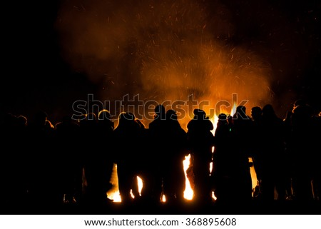 silhouttes of people watching a bonfire,sparks and smoke behind them - stock photo