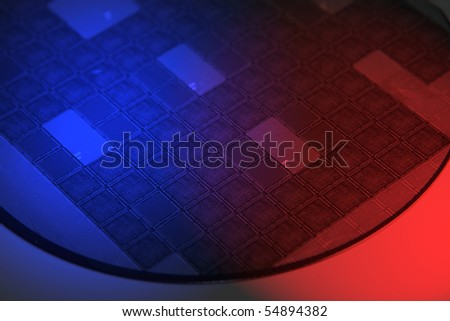 Silicon wafer photographed with red and blue gels - stock photo