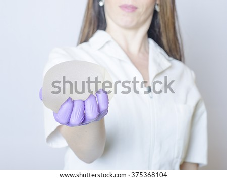 Silicone breast implants. Nurse holding implants. Doctor holding implants. Plastic surgery - stock photo