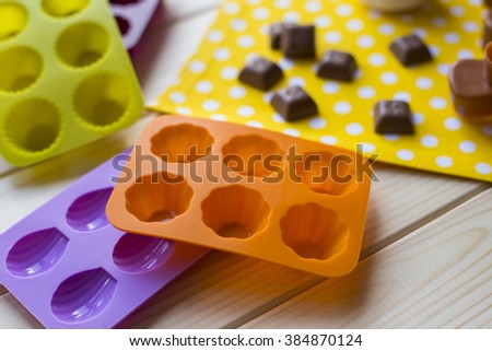 Silicone molds for baking in the form of heart and tools for baking cookies, muffins and cake on a white wooden background - stock photo