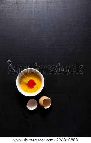 Silicone pastry brush and beaten egg. Baking. against a dark background - stock photo