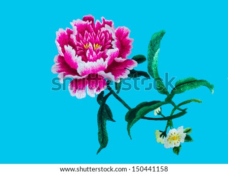 Silk flower sewing by hand on blue background. - stock photo