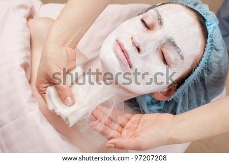 Silk mask applying, beauty treatment young woman face at salon - stock photo