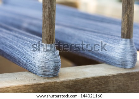 Silk thread and wooden stick - stock photo