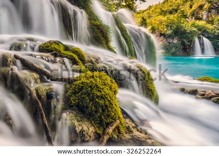 Silk waterfall shot with long exposure over brown rocks with blue pond at Plitvice lakes, Croatia. - stock photo