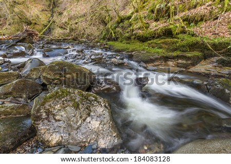 Silky Smooth River Stream with Boulders  - stock photo