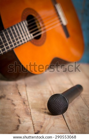 Sill life whit Microphone and classic guitar waiting on wooden floor - stock photo