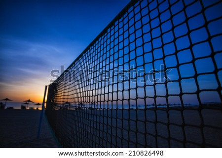 Sillhouette of a volleyball net and sunrise on the beach. summer - stock photo
