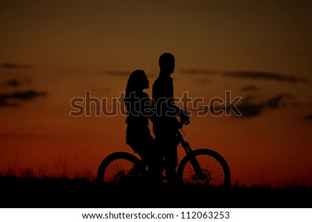 sillhouette of sweet young couple in love standing in the field. sunset (dawn). Outdoor shot