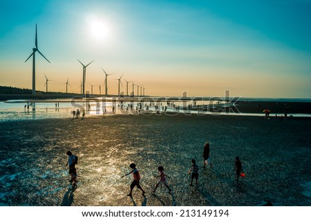 sillouette of Wind turbine array at seashore wetland - stock photo