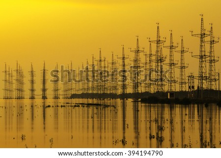 sillouette of Wind turbine at seashore wetland, Impression network at transformer station in sunrise, high voltage up to yellow sky take with yellow tone, horizontal frame  - stock photo
