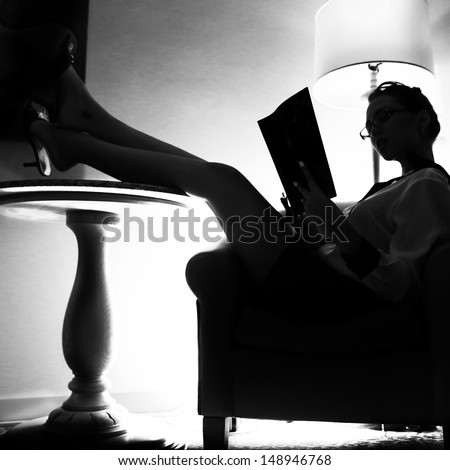 silluette of a woman sitting with her legs up reading a magazine - stock photo