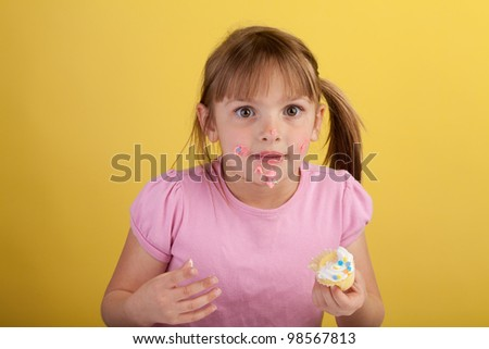 Silly blonde girl eating a cupcake on a yellow background
