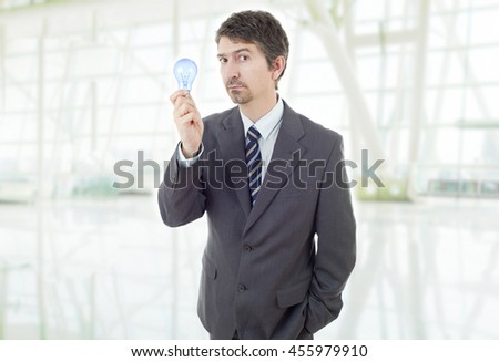 silly business man with a lamp at the office - stock photo