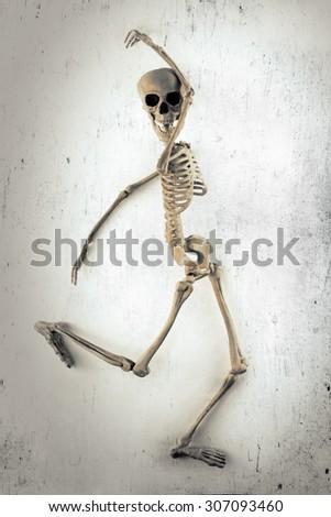 Silly dancing medical skeleton on grunge vintage background - stock photo