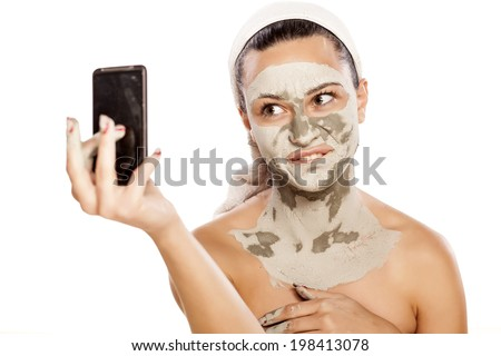 silly girl make selfies with a mask on her face - stock photo