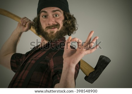 Silly hipster lumberjack gives okay sign while holding axe - stock photo