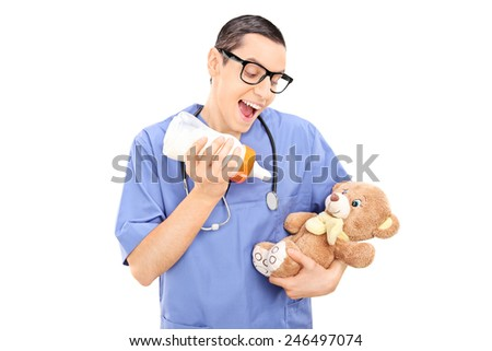 Silly male doctor feeding milk to a teddy bear isolated on white background - stock photo