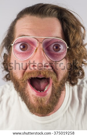 Silly surprised four eyed man wearing glasses - stock photo