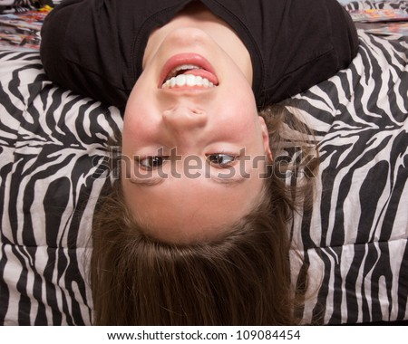 Silly upside down girl against zebra pattern - stock photo