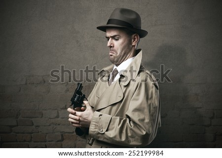 Silly vintage detective pointing a gun to his face and making a dumb expression - stock photo