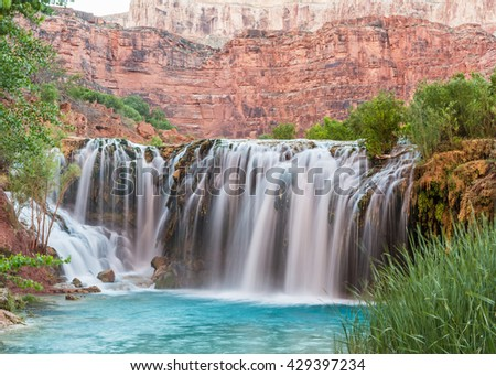 Silly water flows over Little Navajo Falls into a turquoise pool on the Havasupai Indian Reservation in the Grand Canyon.