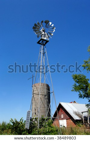 Silo and windmill stand besides a barn overgrown with weeds and grass.  Barn is red, wooden and with a tin roof.  Agriculture in Kansas. - stock photo